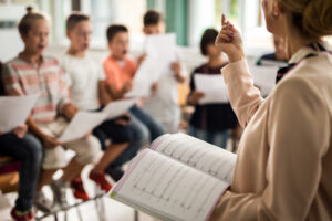 Barn övar körsång. Unrecognizable teacher giving a lesson during music class.