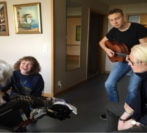 """Arvid Pereswetoff-Morath (guitar), Marcus Wiander (percussion) and Betty Fjällström (vocals) perform music to a woman at an elderly care home in Sundbyberg as part of the """"Meet in Music – Whole Life"""" project. Photo: Ulrika Kron"""