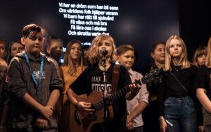 Barn sjunger och spelar musik på scen